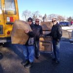 Knights of Columbus holding boxes of coats