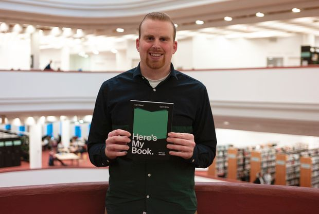 A photo of Michael Jacques holding his book